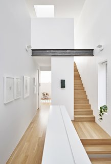 The skylight allows glimpses of sky from multiple points below. The second level is dedicated to bedroom suites.