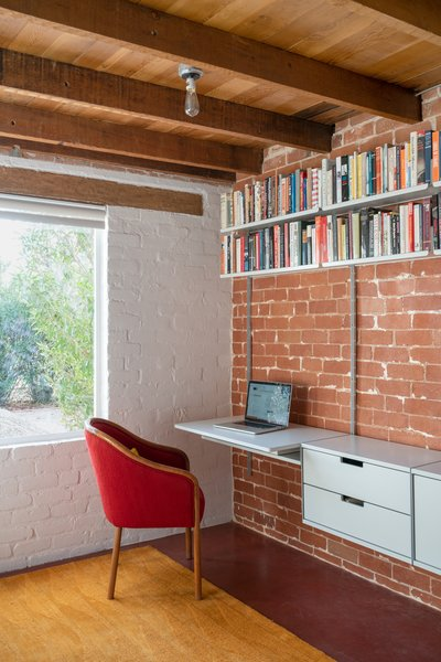 """This room is located in a brick addition that the architects estimate was built in the 1950s. """"Because this space was an addition and of a different material and construction than the original home, we felt exposing and celebrating this difference would be best,"""" says Hazelbaker. They did so by removing a built-in closet, exposing the brick wall, and installing the Vitsoe system that doesn't obscure the difference between old and new."""