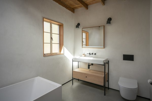 The medicine chest is from Roburn and trimmed out with Douglas fir, similar to the pocket door and window casing. The fixtures are Jason Wu for Brizo, and join a Duravit sink and a wall-mounted toilet by Toto.