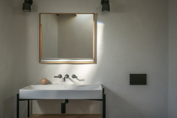 """The custom-designed vanity is composed of powder-coated aluminum and Douglas fir. """"We are makers at heart and cherish the opportunities to create objects that straddle the line between furniture, fixture, and architecture,"""" says Hazelbaker. """"Bespoke and handcrafted details are important to the ethos of our practice."""""""