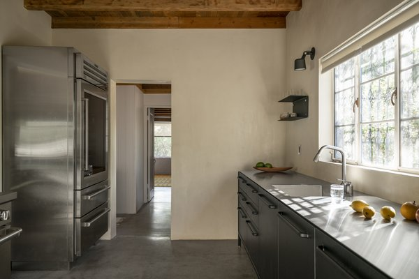 The original wood ceiling was revealed, and the appliances are also freestanding. Shelving and lights are also by Vipp.