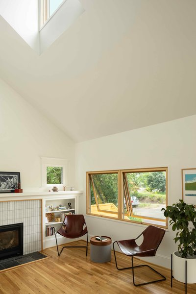 The architects opened up the flat ceiling in the living room and inserted a multipurpose dormer. Ann Sacks tile now surrounds the fireplace.
