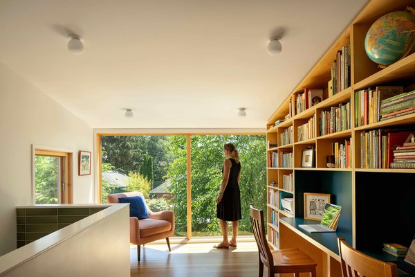 The upper floor layout was rejiggered so that the kids' bedroom could be relocated, and now a cantilevered addition at the back of the house hosts a library space with full-height glass capturing a view to the backyard. The built-in shelving has a rich blue laminate, and the tiled wall to the left denotes the light well into the kitchen.