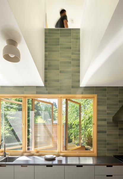 A ceiling cut-out connects the lower-level to an upstairs library/hang-out space, and also fashions a light well lined in Heath Ceramics tile.