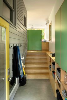 This reconfigured Craftsman home in Portland, Oregon, designed by Beebe Skidmore Architects, includes a highly functional mudroom. The exterior siding and windows were kept in place to reference the house's previous incarnation. Built-in cabinetry with exposed plywood edges and laminate fronts are now up to the task of handling the family's gear. The mudroom has sight lines to the family nook at the back corner.