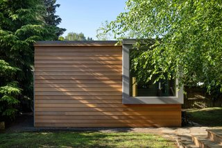 Now, there's an office space and a sauna inside a small backyard shed, which delivers privacy to occupants. The materials and oversized window visually connect the smaller structure to the new facade of the main building.