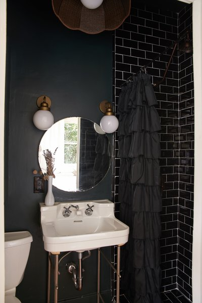In the smaller bathroom, Rossi embraced the cozy with dark paint and subway tile.