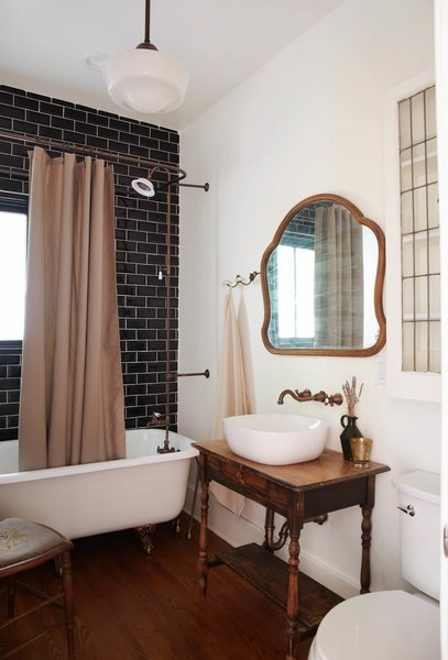 A wall of black subway tile in this bathroom keeps the scheme consistent with the other one.