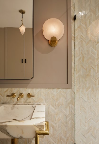 The bathroom features an alabaster and unlacquered brass Melange sconce by Kelly Wearstler.