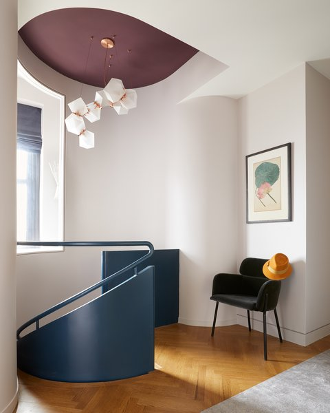 The design team subtly sculpted the wall around the top of the staircase. A CB2 Azalea Gray Mink chair sits in the hall.