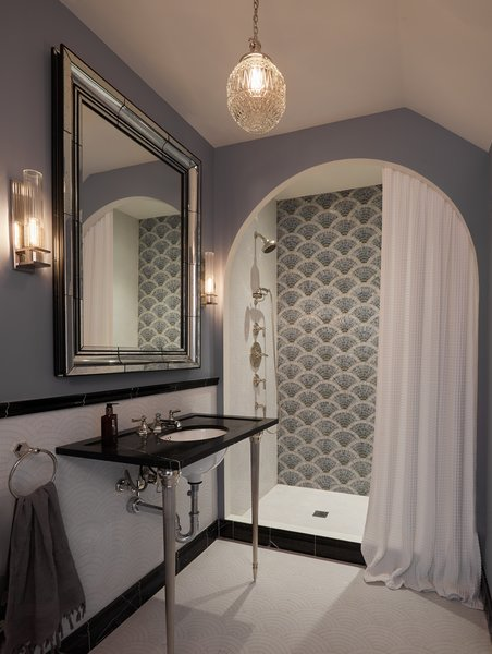 Artistic Tile's Blue Fan Club glass mosaic tile is a focal point in the shower. The sink console is composed of Nero Marquina marble and polished nickel by Michael Smith For Town by Kallista. The polished nickel hardware is also by Michael Smith For Town. Above the sink, Sperry wall sconces by Hudson Valley Lighting flank a Restoration Hardware glass moulded mirror. The ceiling light is vintage.
