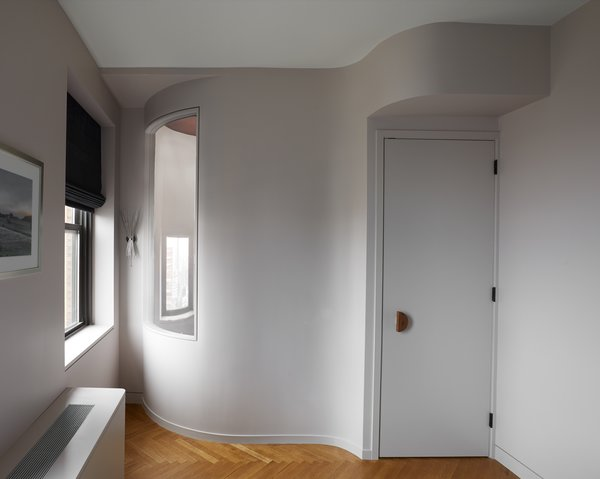 An interior window conveys natural light into the hallway from an exterior window in the bedroom. Curving walls allow the relatively small space to live larger. The custom door pull is fashioned from walnut.