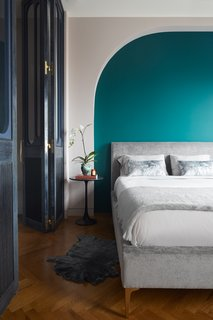 "A shade of ""Art Deco green"" bedecks the wall behind the gray velvet Andes Deco bed by West Elm."