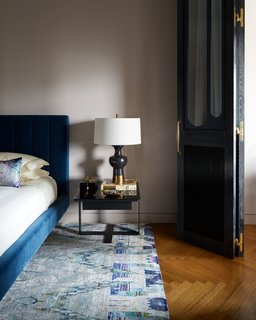 In the adjoining sleeping area, a one-of-a-kind rug woven from recycled sari silk, sourced from ABC Carpet, lies beneath a Hartley Bed from Room & Board in indigo velvet. The Pablo Lamp by Arteriors rests atop a steel-and-black-glass end table by Caligaris.