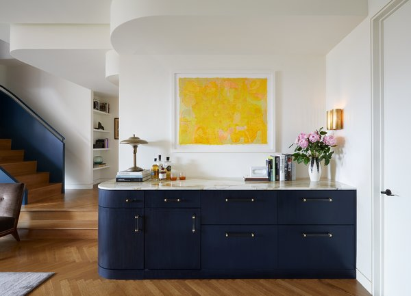 A marble bar hosts three Sub-Zero refrigerator drawers and one freezer behind indigo cerused cabinet fronts, which contrast with the artwork by Irving B. Hayes.