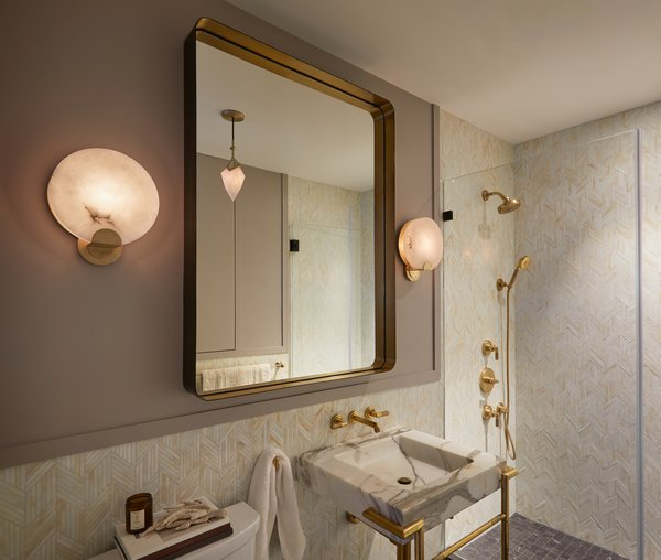 The revamped bathroom features Ann Sacks Lume glass mosaic tile on the walls and Artistic Tile's Belgium Blue Matte on the floor. A Restoration Hardware Varese brass-and-bronze mirror hangs above the Calacatta gold marble and unlacquered brass vanity by Kallista.