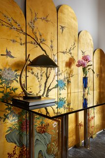 In the hallway, a vintage Art Deco desk made of nickel, brass and smoked glass stands before a vintage Chinoiserie hand-painted screen.