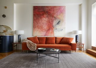 "The Irving sofa by Verzelloni sits between vintage Scandinavian rosewood end tables with interior pull-out trays. The large, abstract artwork is a 1970's oil painting by ""Unknown."""