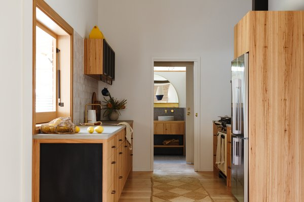 The bathroom door is now centered on the rear wall, and an intermediary pantry space buffers the bathroom from the kitchen. The upper cabinets to the side of the sink have mesh inserts.
