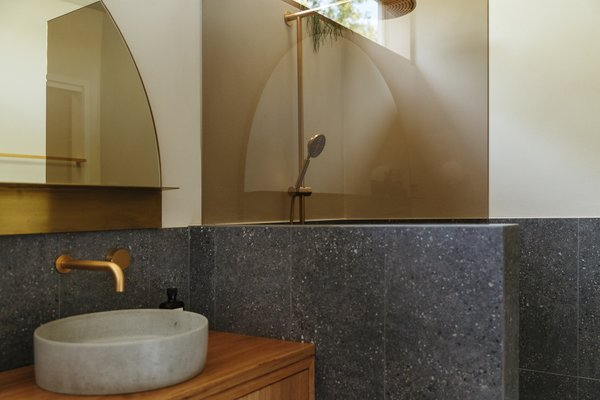 The walls and floor are covered in large-format Cerbis Ceramics Frammenti tile. The upper walls have a Wall2Floor Render finish from Adelaide Custom Coatings. The blackbutt vanity by Timberwolf Design sports a Studio Bagno Silo Nucrete basin concrete sink.