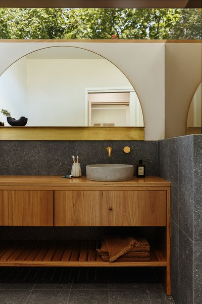 "A custom arch mirror in brass from Pop & Scott makes an eye-catching statement in the new bathroom. ""The introduction of a curve was very important to break up all the lines and soften the bathroom space,"" says Harry."