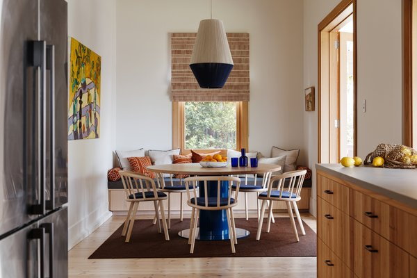 In the new dining area, a Dreamweaver pendant from Pop & Scott is suspended over an Agostino & Brown Jam table in oak with a navy powder-coated base. Bleached ashwood Nym chairs by Pedrali surround the table.