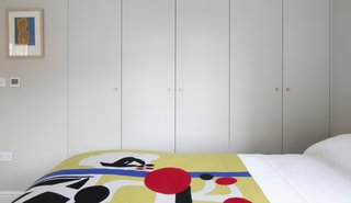 """For storage, IKEA carcasses were wrapped with painted MDF exteriors for a streamlined appearance. """"The new, simplified design with the doors painted the same color as the wall means the wardrobes are less dominant,"""" says Astrain. """"This helps the room feel less crammed, calmer, tidier, and bigger."""""""