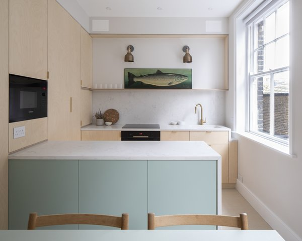 "In the kitchen, bespoke plywood panels wrap IKEA cabinet inserts for a high-end feel on a budget. ""The kitchen is a collection of very intricate details,"" says Astrain, who fitted the space down to the last available millimeter. The space benefits from two windows now, thanks to the relocated dining area."