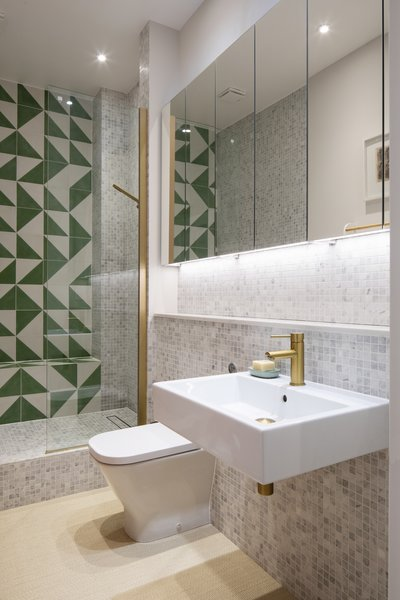 "Astrain outfitted the relocated bathroom with marble mosaic tile and a punchy Bert and May Green Alalpardo tile in the shower as a graphic accent. ""The client kept saying she liked geometric patterns—no flowers, etc.—and some bold color,"" says Astrain."