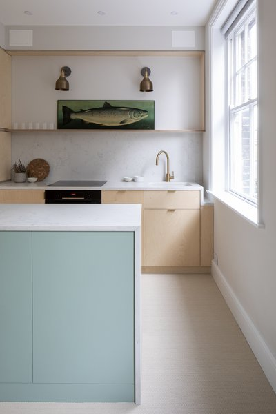 The backsplash and counters look like marble but are actually hardworking quartz. A drop in the counter gives breathing room to the window. The soothing, mint shade of paint is Little Greene Aquamarine Deep.