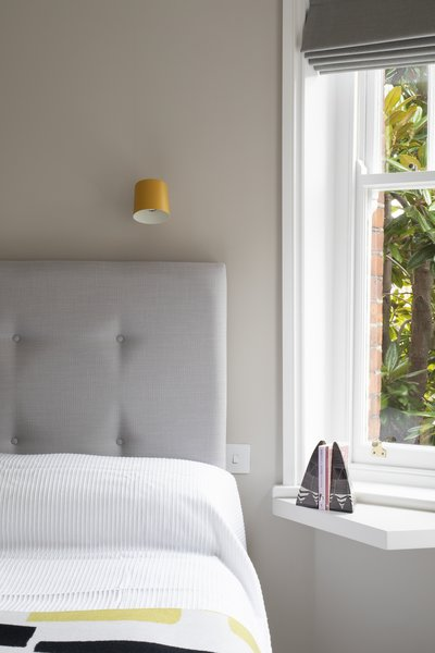 A funky, angled shelf sits under the window by the bed, creating a nightstand.