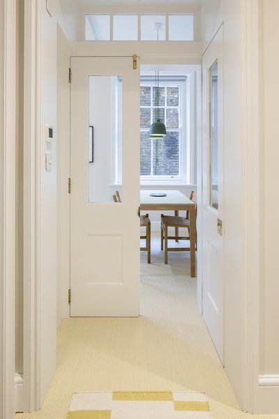 "A new transom window over the doorway brings much-needed light into the hallway, and the doors pocket into the walls for unimpeded flow, which is even more crucial in a small space. ""[They] help the flat feel more sleek and less cluttered,"" says Astrain. The new doors also comply with building regulations—there needed to be a fire door between the kitchen and hallway."