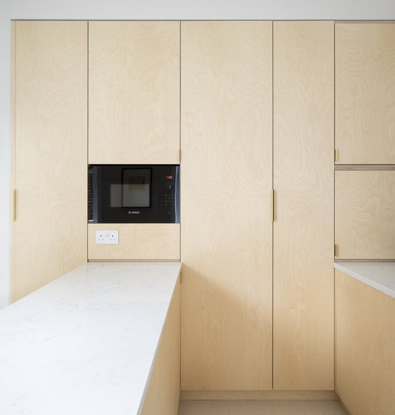 A Bosch microwave is sleekly inset into the wall of storage.