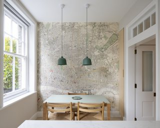In its new location, the table can comfortably seat four and enjoy the view out the window. The wall covering is a Victorian London map by Hamilton Weston circa 1862. Its coloring synchs well with the tabletop and the pendants, which are Jens Fager for Muuto.