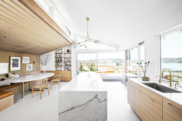"Marble counters, custom white oak cabinetry, and terrazzo tile flooring from Ann Sacks brighten up the kitchen. ""Their light tones were the right balance of Southern California modernism with the warmer, highly crafted wood carpentry that the Puget Sound region is known for,"" says Wittman."