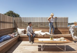 """Ipe wood decking and a built-in bench were combined with a vertical cedar slat screen, which """"obscures the neighboring houses at the precise height of their rooflines, while allowing sunlight to filter through,"""" says Wittman. A custom-designed, live-edge table has Lucite legs."""