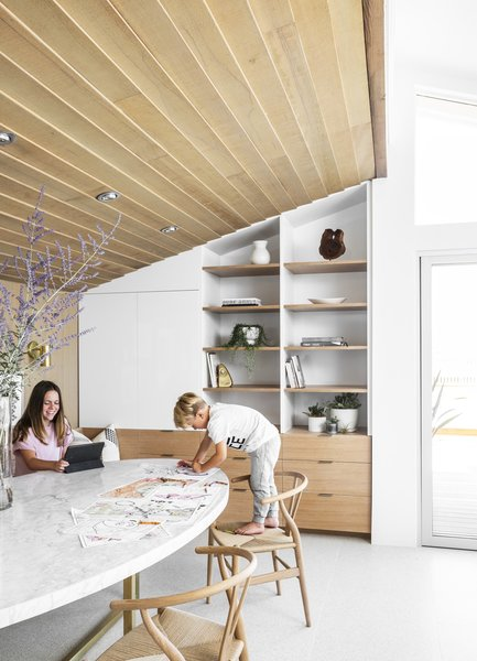 "The built-in shelving and storage unit was redesigned. ""The idea was to make it a very multifunctional space,"" says Wittman of the dining nook, where kids can do homework or watch a movie, and grown-ups can gather for dinner around the large table."