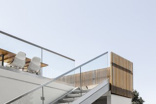 "The staircase, with precast concrete steps, now leads down to the future pool terrace. ""We sought to connect the spaces so the family could be relaxed and meander barefoot through the property,"" says Wittman."