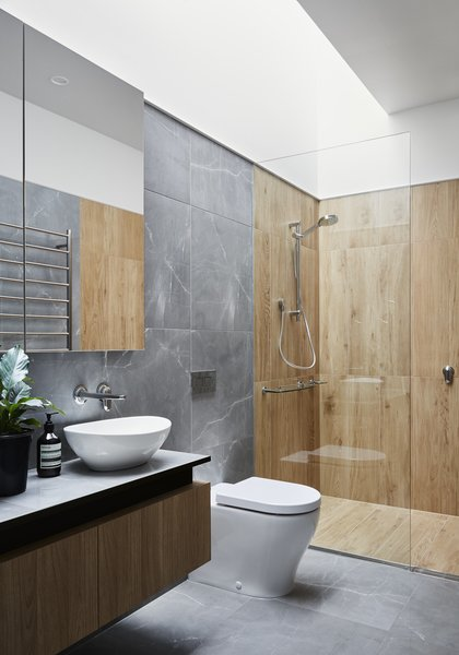 The floor, walls, and vanity in the master bathroom all sport the same porcelain tile for visual consistency, while textured porcelain tiles that look like wood distinguish the shower. A new skylight sheds light inside the internal room.