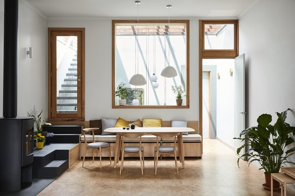 Tsai Design relocated the bedroom. In its place are the main living areas, including the dining room seen here. A built-in bench tucks neatly beneath the interior window.