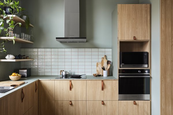 A warm palette of birch plywood with olive green linoleum outfits the kitchen.
