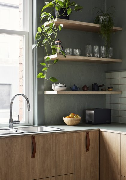 Simple leather pulls adorn the cabinet faces, while open shelves put everyday items within easy reach.