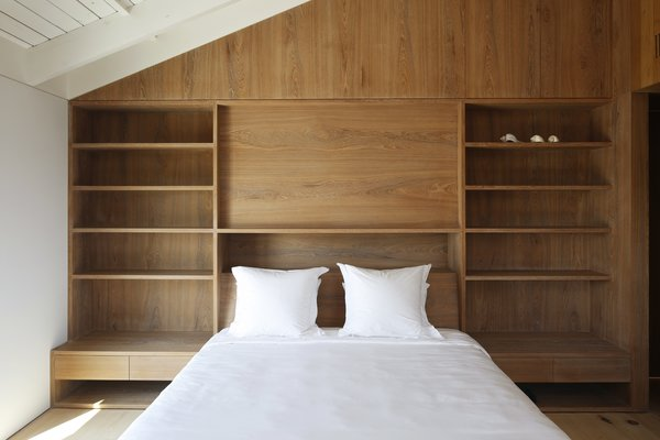 """The team removed dropped ceilings in the relatively small bedrooms and painted the exposed rafters a glossy white to bounce light. """"Opening the ceiling makes the [bedrooms] feel much bigger,"""" says Chernak."""