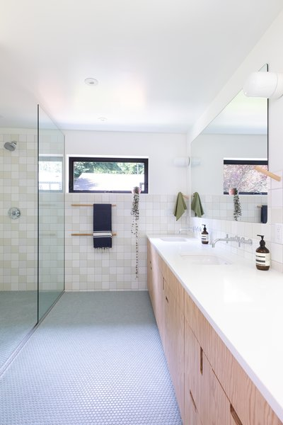 The Caesarstone and plywood vanity echoes the materials in the kitchen, as does the wall tile.
