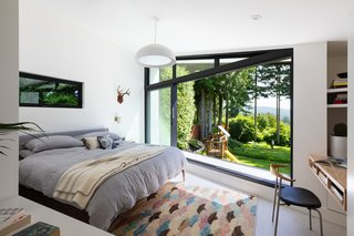 "The angled wall of the addition frames excellent sightlines into the backyard and beyond. ""That bedroom had a point of prospect that allowed for it to reach out to the long view,"" says Cuddington. The bedside sconces are Schoolhouse Electric, and the pendant is from Ross Gardam."