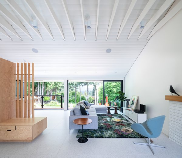 The team removed the dropped ceiling and attic above to expose the tongue-and-groove paneling and the supports at the roof. A Swan Chair by Fritz Hansen sits with the client's sofa and USM media cabinet.