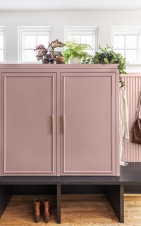 There's now a storage locker for each member of the family. They sit atop a platform made of stained oak, like the kitchen island. The cabinet maker customized the molding detail to match the width of the pulls.