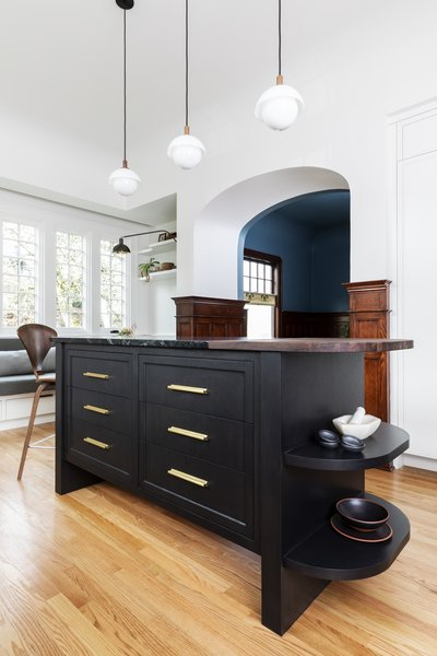 Dyer Studio custom-designed the island with a black-stained white oak wood base and a walnut and soapstone counter that curves at both ends.