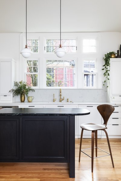 The team added a bank of windows above the sink to flood the room with light. The ceiling pendants are from Allied Maker and the stool is the Cherner Counter Stool from Design Within Reach.