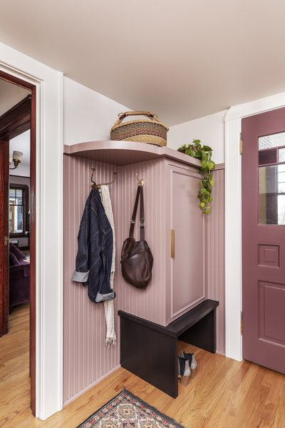 """The renovation of a Victorian-era home in Portland, Oregon, included updating the entry area with new storage and a muted pink hue, picked in collaboration with the client. """"She wasn't afraid of color,"""" says Stephanie Dyer of Dyer Studio, who paired it with a deeper burgundy shade for the doors."""